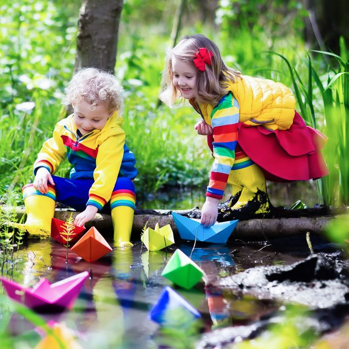 Children play with colorful paper boats on a spring day
